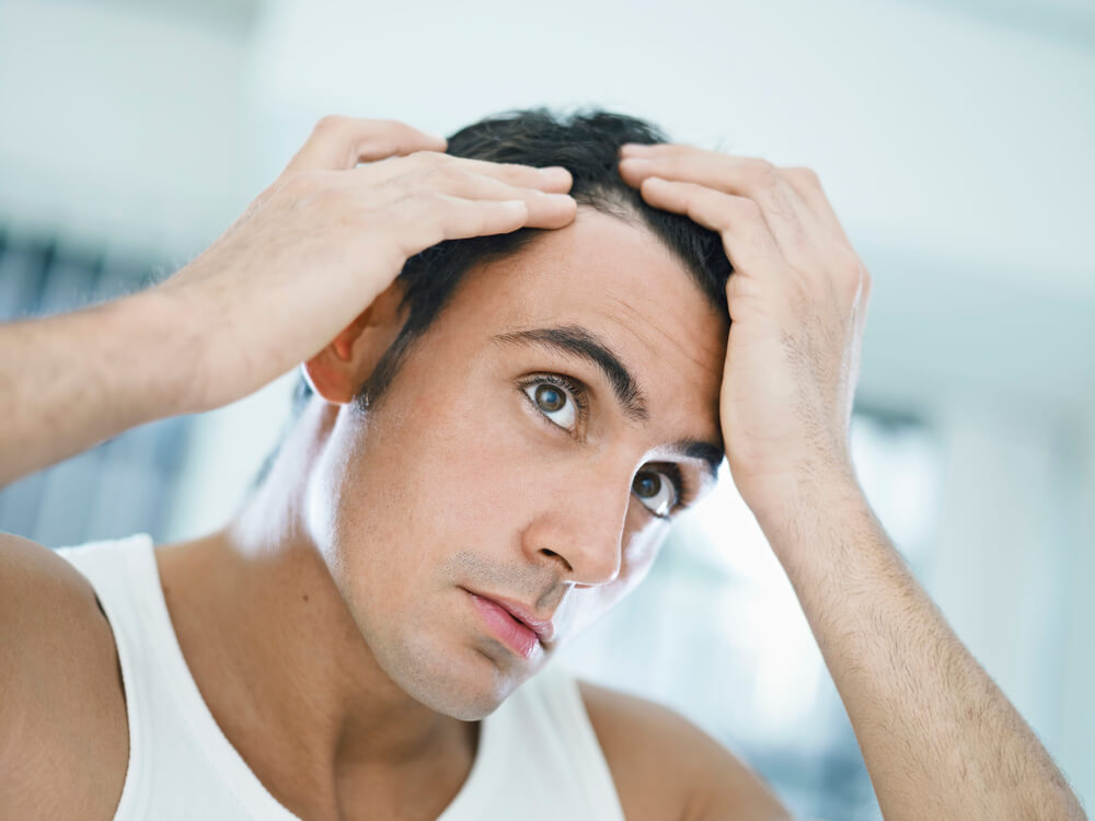 A man inspecting his receding hairline